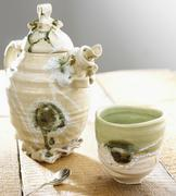 Pottery teapot with tea cup and spoon - stock photo