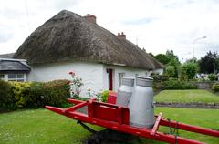 Thatch Roof Cottage and Milk Jugs Stock Photos