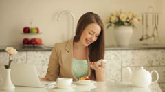 Beautiful girl sitting at kitchen table with laptop holding mobile phone Stock Footage