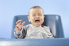 Baby boy (6-11 months) in high chair crying, eyes closed - stock photo