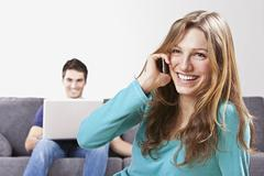 Stock Photo of Woman talking on mobile phone, man using laptop in background