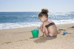 France, Corsica, Girl (2-3) playing with sand on beach - stock photo