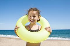 France, Corsica, Girl (2-3) wearing inner tube, smiling, portrait - stock photo