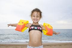 France, Corsica, Girl (2-3) wearing armbands on beach, smiling, portrait - stock photo
