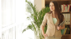 Cheerful young woman in formalwear standing in front of window holding touchpad - stock footage
