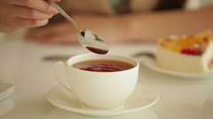 Young woman stirring tea with spoon - stock footage