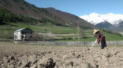 Woman gardening in dry field in Georgia Stock Footage