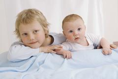 Germany, Boy (2-3 Years) and baby boy (2-5 Months) lying on bed - stock photo