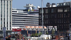 Cruise ship sailing at the IJ Amsterdam behind Westerdok apartment building Stock Footage