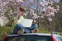 Stock Photo of Germany, Boy sitting on car roof and using laptop with magnolia tree in