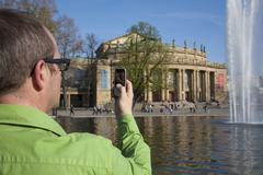 Germany, Stuttgart, Senior man capturing image of opera house from cell phone Stock Photos