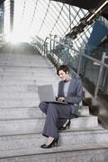 Germany, Bavaria, Munich, Business woman at subway station using laptop, sitting Stock Photos