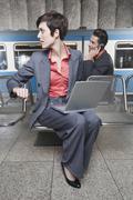 Germany, Bavaria, Munich, Business people at underground station platform using Stock Photos
