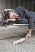 Germany, Bavaria, Munich, Business man at subway station sleeping on bench - stock photo