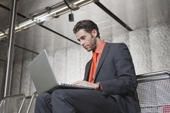 Germany, Bavaria, Munich, Business man at subway station using laptop Stock Photos