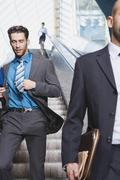 Germany, Bavaria, Munich, Three businesspeople on escalator, one of them running - stock photo