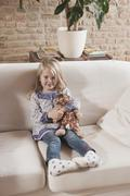 Stock Photo of Germany, Cologne, Girl (4-5) with a stuffed toy, sitting on sofa