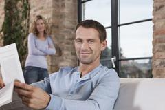 Germany, Cologne, Couple, man on sofa holding newspaper, woman standing in Stock Photos