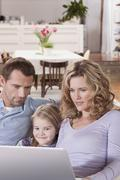 Germany, Cologne, Family on sofa using laptop, portrait - stock photo