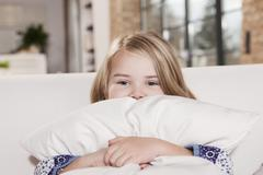 Stock Photo of Germany, Cologne, Girl (4-5) on sofa holding cushion, portrait, close-up