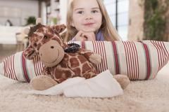 Germany, Cologne, Girl (4-5) with a stuffed toy, lying on carpet Stock Photos