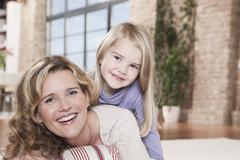 Stock Photo of Germany, Cologne, Mother and daughter (4-5) at home, smiling, portrait, close-up