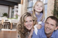 Germany, Cologne, Family in living room, laughing, portrait, close-up - stock photo