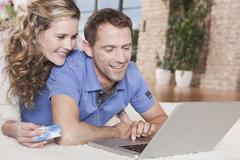 Germany, Cologne, Couple lying on carpet using laptop, portrait - stock photo