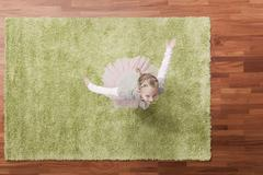 Germany, Cologne, Girl (6-7) playing on carpet, looking up, elevated view - stock photo