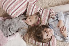 Germany, Cologne, Boy and girl (6-7) lying on carpet, elevated view - stock photo