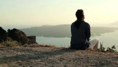 Alone woman sitting on cliff and looking at sea HD Stock Footage