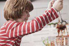 Germany, Cologne, Boy (6-7) serving spaghetti, side view - stock photo