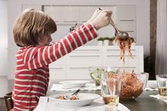 Stock Photo of Germany, Cologne, Boy (6-7) serving spaghetti, side view