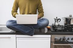 Man sitting on kitchen worktop, using laptop Stock Photos