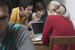 Friends using laptop. - stock photo