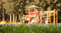 Children having fun on playground in park. Selective focus on foreground. Footage