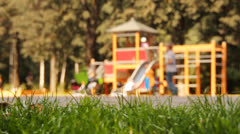 Children having fun on playground in park. Selective focus on foreground. - stock footage