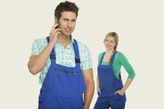 Man in overall using mobile phone, woman standing in background Stock Photos