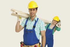 Man and woman in overall carrying timber, smiling, portrait - stock photo