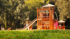 Children having fun on playground in park. Selective focus on foreground. Stock Footage