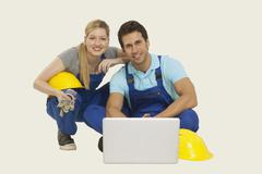 Man and woman in overall using laptop, smiling, portrait Stock Photos