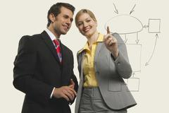 Businessmen and women discussing, women pointing. - stock photo