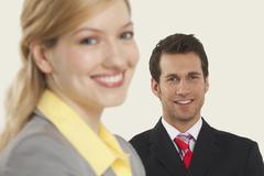 Stock Photo of Businesswomen smiling, men in behind.