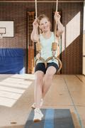 Germany, Emmering, Girl (12-13) hanging from flying rings, smiling, portrait Stock Photos