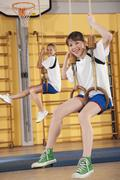 Germany, Emmering, Girls (12-13) hanging from gymnastic rings, smiling, portrait - stock photo