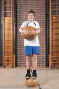 Germany, Emmering, Teenage boy (14-15) holding ball, portrait - stock photo