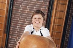 Germany, Emmering, Teenage boy (14-15) lifting ball, portrait - stock photo