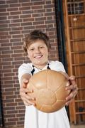 Germany, Emmering, Teenage boy (14-15) holding ball, portrait Stock Photos