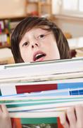 Germany, Emmering, Boy (12-13) holding stack of books, portrait, close up Stock Photos