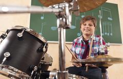 Germany, Emmering, Teenage boy (14-15) playing drumset, portrait, smiling Stock Photos